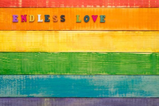 Drewniane tło w kolorach tęczy lgbt, z napisem nieskończona miłość w lewym górnym rogu, miejsce do kopiowania, układ płaski, widok z góry