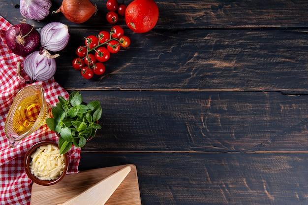 Drewniane tło ze składnikami do pizzy. szare drewno z serwetką w czerwoną kratkę. skopiuj miejsce. widok z góry