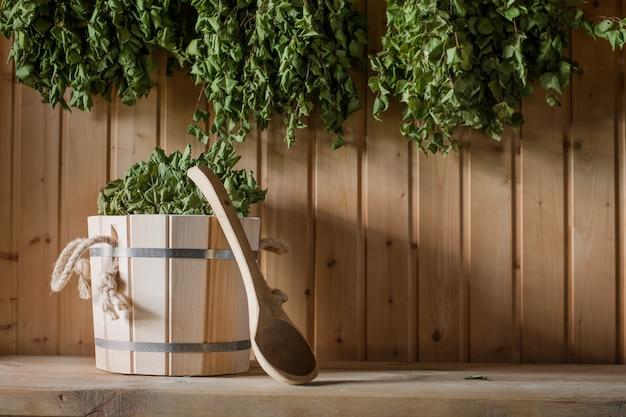 Drewniane wiadro i brzozowa miotła w rosyjskiej łaźni. sauna.
