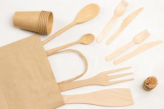 Drewniane widelce i noże w papierowej torbie. jednorazowa zastawa stołowa na piknik, fast food.