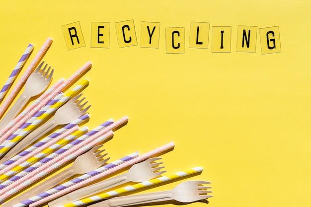 Drewniane widelce jednorazowe na żółtej ścianie, recykling i koncepcja przyjazna dla środowiska. zero odpadów, przedmioty bez plastiku, zatrzymaj plastik. widok z góry. miejsce na tekst. organiczne, ekologiczne przyjęcie, zakupy