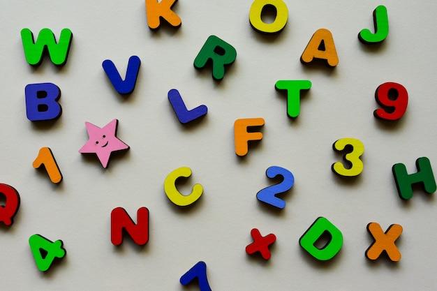 Drewniane wielokolorowe litery i cyfry na beżowym tle. gra edukacyjna dla szkoły podstawowej. dzień dziecka.