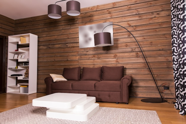 Drewniane wnętrze pokoju, brązowa kanapa i stylowy biały stolik w kształcie schodów