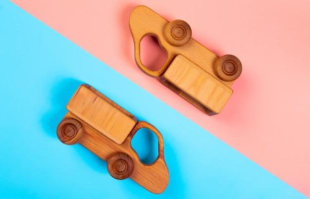 Drewniane zabawki ciężarówki na na białym tle wielokolorowe żywe tło geometryczne.