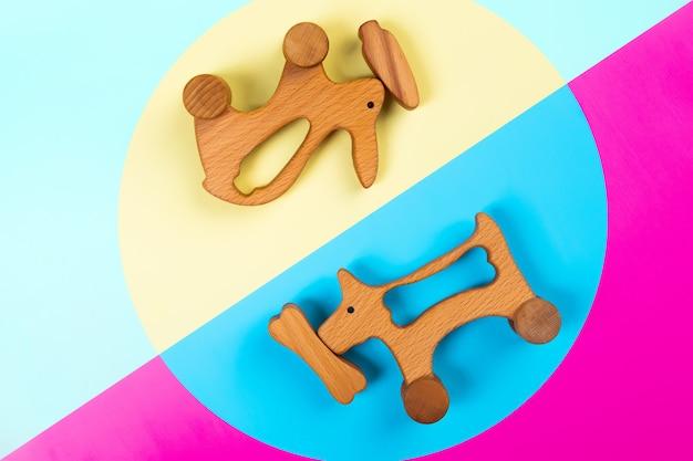 Drewniane zabawki królik z marchewką, psem z kością na różowym, niebieskim i żółtym na białym tle.