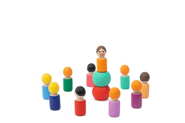 Drewniane zabawki stoją i czekają na polecenia od swojego przywódcy. budowanie zespołu przed liderem. koncepcja podporządkowania człowieka prezydentowi.