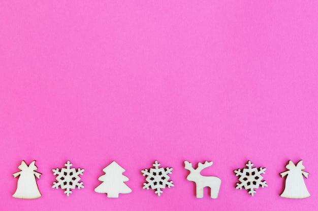 Drewniane zabawki świąteczne na różowym tle, widok z góry, płaskie lay, minimalna koncepcja nowego roku, do projektowania, makiety lub pocztówki