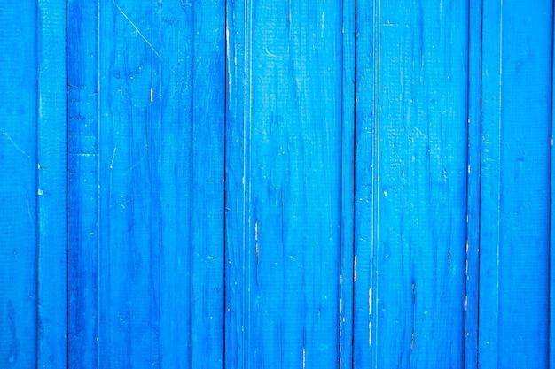 Drewniane zabezpieczenie na całym tle, pomalowane na kolor jasnoniebieski. stara popękana niebieska farba na podłogach drewnianych.