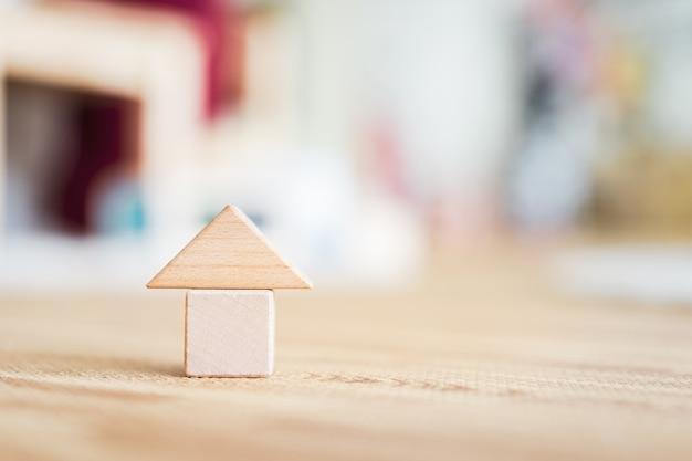 Drewnianego domu model na drewnianym tle, symbol dla budowy