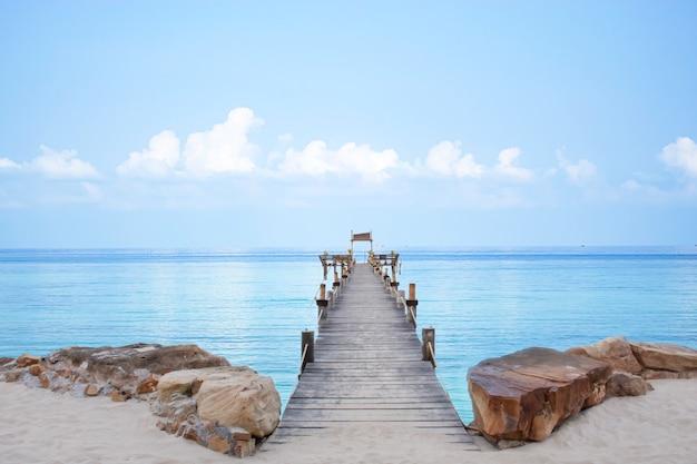 Drewnianego mosta mola łódź w morzu i jaskrawym niebie przy koh kood, trata w tajlandia.