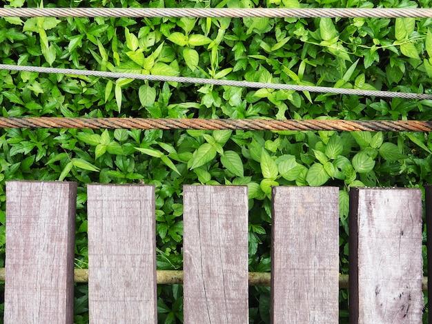 Drewnianego mosta zakończenie up, starzy drewna i ośniedziali kable z zielonym liścia tłem.