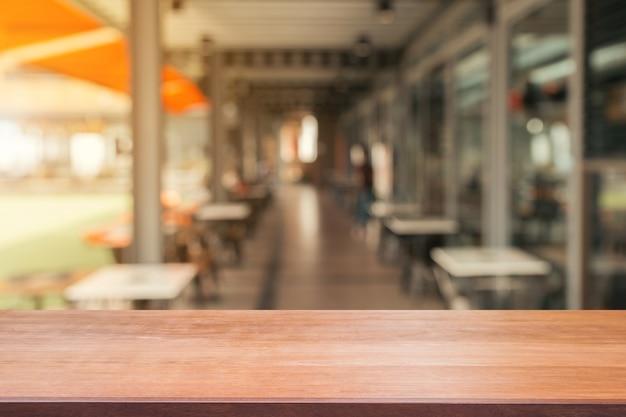 Drewnianej deski pusty stołowy wierzchołek zamazany tło dalej. perspektywiczny brown drewno stół nad plamą w sklep z kawą tle - może używać dla wystawiających produktów pokazu lub projekta kluczowego wizualnego układu projekt.