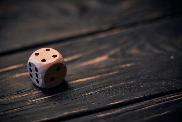 Drewniani kostka do gry na starym drewno stole. numer cztery na górze.