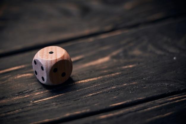 Drewniani kostka do gry na starym drewno stole. numer jeden na górze.
