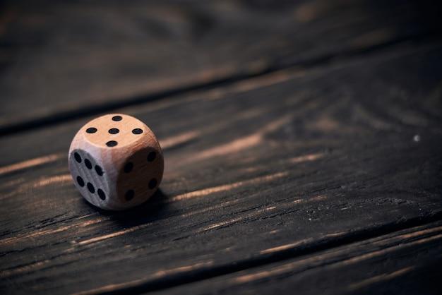 Drewniani kostka do gry na starym drewno stole. numer pięć na górze.