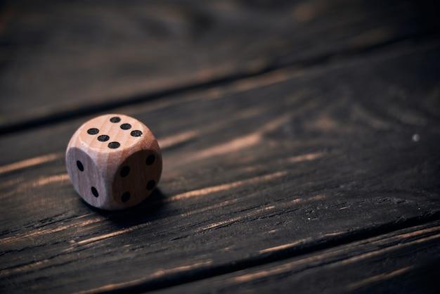Drewniani kostka do gry na starym drewno stole. numer sześć na górze.
