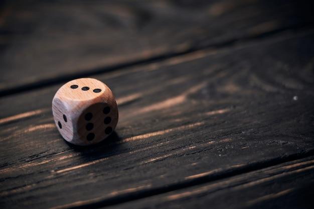 Drewniani kostka do gry na starym drewno stole. numer trzy u góry.