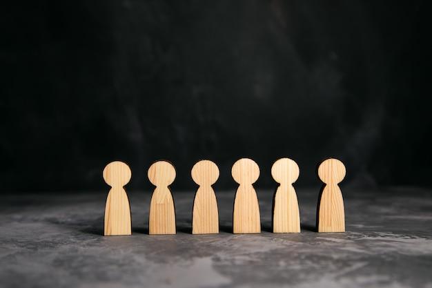 Drewniani ludzie podpisują się na szarym tle stołu