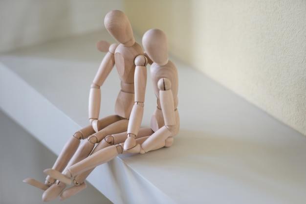 Drewniani ludzie siedzi w domu i ściska. koncepcja relacji ludzi