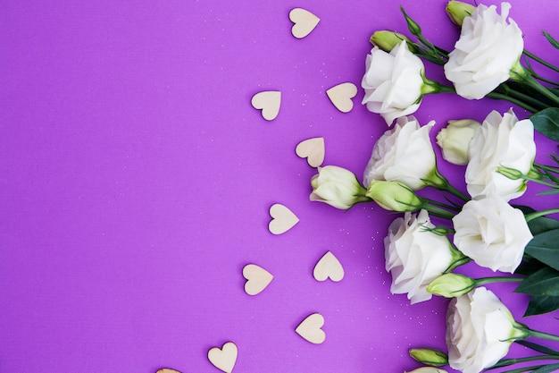 Drewniani serca i kwiaty na purpurowym tle z kopii przestrzenią dla teksta. walentynki, ślub, pojęcie miłości