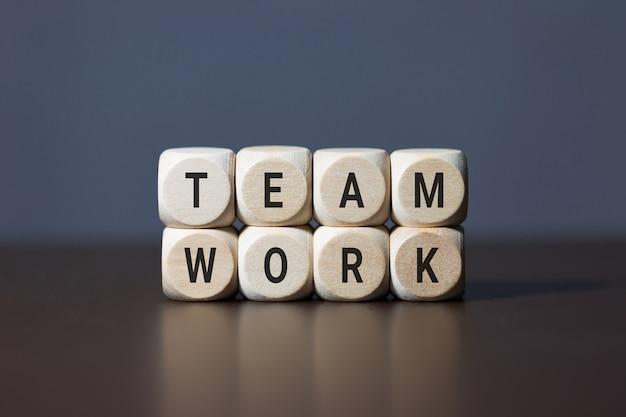 Drewniani sześcianów elementy z listem na drewnianym stole który reprezentuje pracę zespołową. pomysł na biznes.