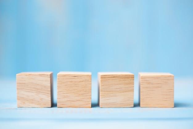 Drewniani sześciany na błękita stołu tle z kopii przestrzenią dla teksta