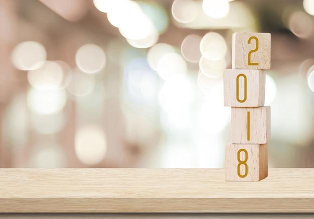 Drewniani sześciany z 2018 na perspektywicznym drewnie nad plamy bokeh tłem z kopii przestrzenią dla teksta, nowego roku szablon