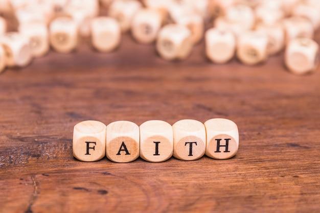 Drewniani sześciany z słowo wiarą na stole