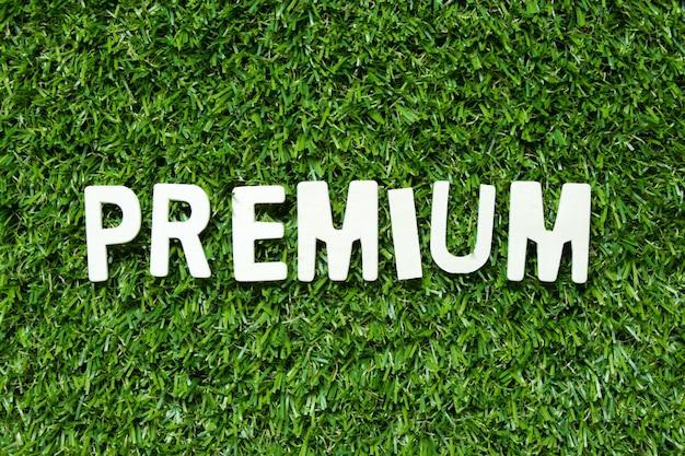 Drewniany abecadło list w słowo premii na sztucznej zielonej trawie