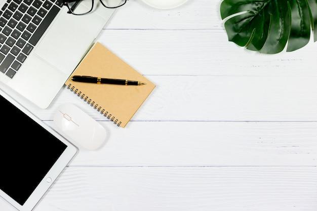 Drewniany biały biurko z pustym notatnikiem i innymi artykułami biurowymi