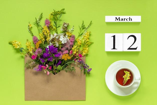 Drewniany biały kalendarz 12 marca. filiżanka herbaty, koperta kraft z wielobarwnymi kwiatami na zielono