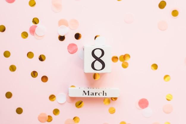Drewniany biały kalendarz z datą 8 marca na różowym tle z konfetti. pojęcie tego samego święta, piękna, miłości i feminizmu. copyspace, szablon