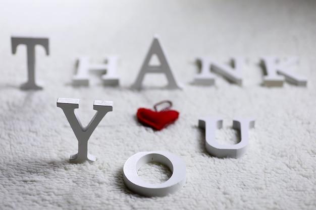 Drewniany biały list dziękuję na zmiętym dywanie na podłodze