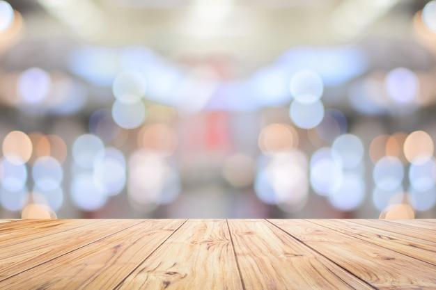 Drewniany blat kontuar na jaskrawego bokeh wewnętrznym tle z białym stołowym blatem