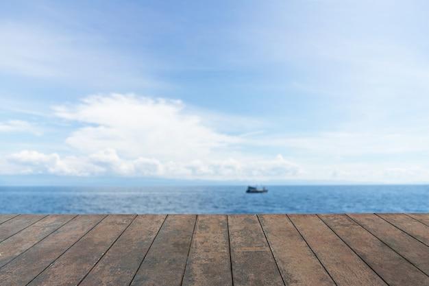 Drewniany blat, krajobraz uroda pod błękitne niebo chmury, tło błękitnego morza.