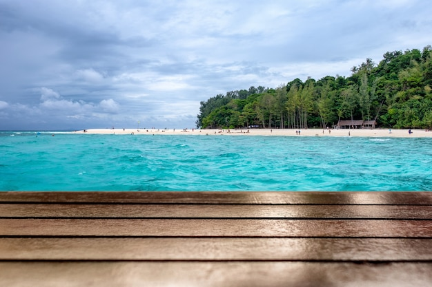 Drewniany blat na pięknej plaży morskiej w tle bambusowej wyspy