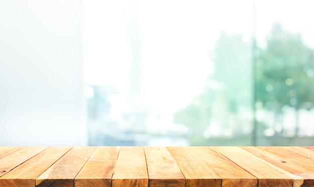 Drewniany blat na rozmytym szkle okiennym, tło ściany z widokiem na miasto do montażu ekspozycji produktu lub projektowania kluczowych układów wizualnych
