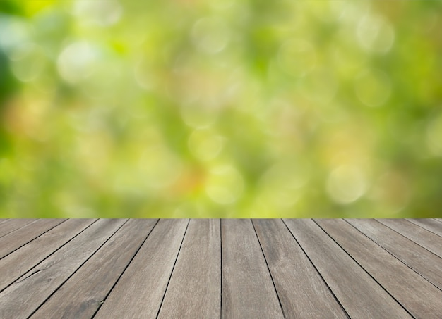 Drewniany blat stołu i zielony niewyraźne tło bokeh
