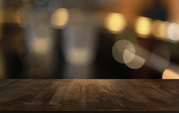 Drewniany blat w rozmycie tła pokoju wnętrze z pustą przestrzeń kopii.