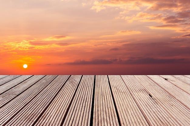 Drewniany blat z kolorowym dramatycznym niebem z chmurą przy zmierzchem