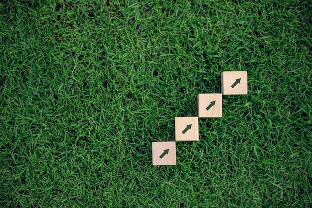Drewniany blog z ikona przyrostem na trawy tle.