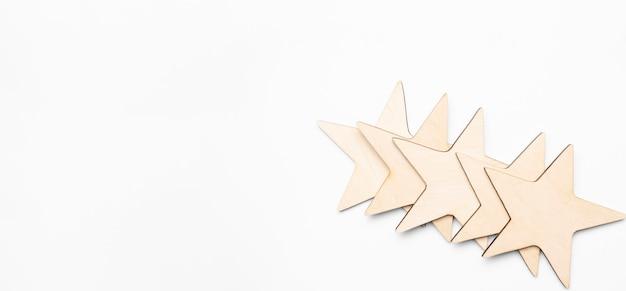 Drewniany blok pięciogwiazdkowy kształt na drewnianym stole szarym tle. blok 5 gwiazdek ocenił najlepszą koncepcję doskonałości usług. nagroda dla klientów excellence w głosowaniu zwycięzców w zakresie satysfakcji z jakości.