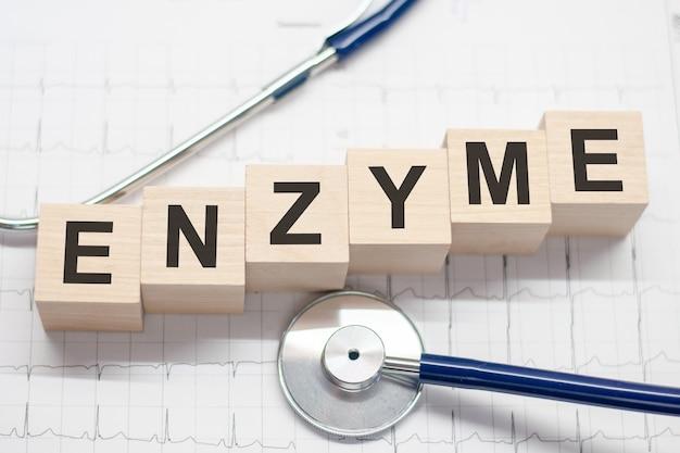 Drewniany blok tworzy słowo enzym ze stetoskopem na pulpicie lekarza koncepcyjnego opieki zdrowotnej dla kliniki szpitalnej i biznesu medycznego medical