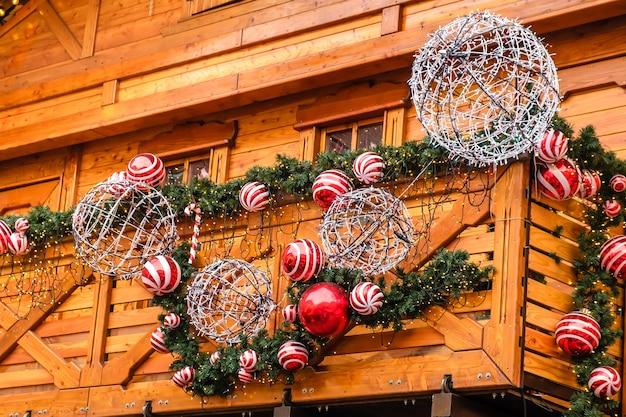 Drewniany budynek restauracji w stylu vintage ozdobiony sztuczną jodłą z girlandą i wieloma czerwonymi i białymi bombkami w zimowy dzień, bez śniegu.