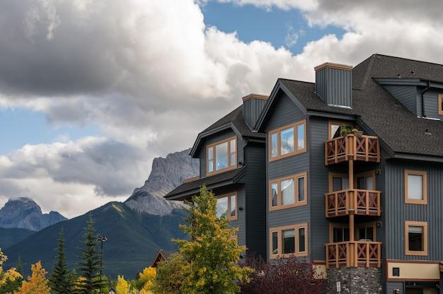 Drewniany budynek ze skalistymi górami w jesiennym lesie w centrum miasta w canmore, kanada