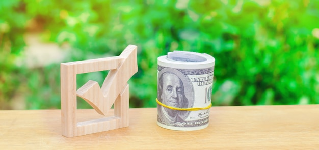 Drewniany checkbox i pieniądze. przyciąganie zasobów i zasobów w celu rozwiązania problemów.