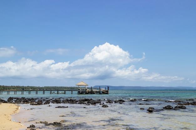 Drewniany chodnik który prowadzi do morza od plaży z dużą białą chmurą w tle.