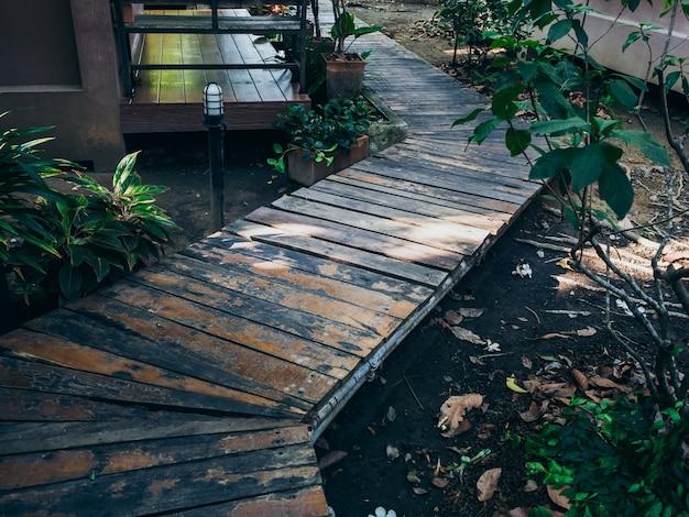 Drewniany chodnik z deski między zielonym ogrodem w domu.