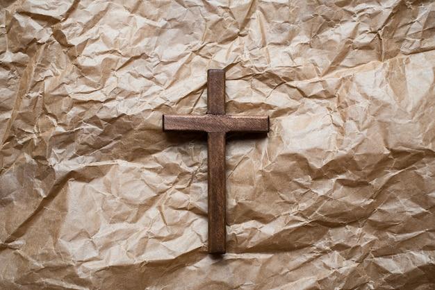 Drewniany chrześcijański krucyfiks na białym tle na papierze do pakowania.
