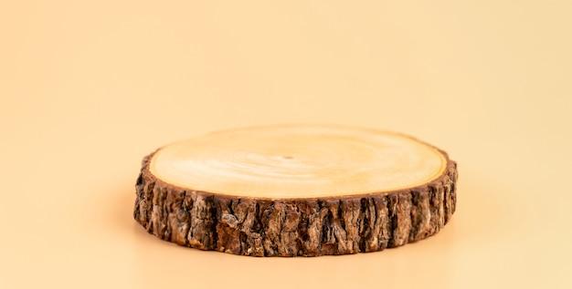 Drewniany cokół na pomarańczowej ścianie, pokaz produktów kosmetycznych.
